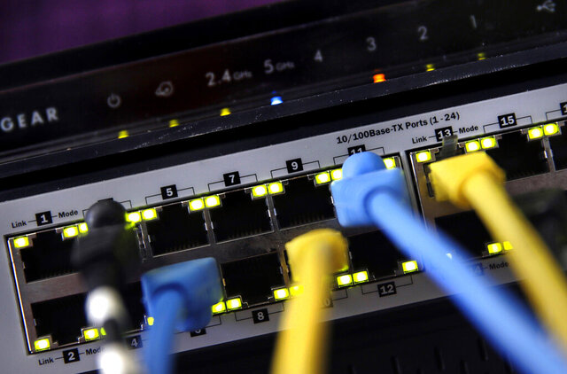 FILE - In this June 19, 2018, file photo, a router and internet switch are displayed in East Derry, N.H.   With so much of the U.S. workforce,  and their families, now cooped up at home to combat the spread of  coronavirus, it's not a huge surprise that home internet is showing the strain. Will there be a bandwidth problem with all the devices going at once?  (AP Photo/Charles Krupa, File)