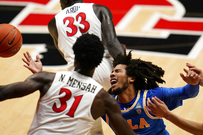 UCLA guard Tyger Campbell, right, loses control of the ball as San Diego State forward Nathan Mensah (31) defends during the first half of an NCAA college basketball game Wednesday, Nov. 25, 2020, in San Diego. (AP Photo/Gregory Bull)