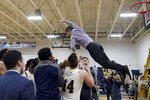 In this Thursday, Feb. 27, 2020 photo, Merrimack College head coach Joe Gallo leaps from a ladder into his players' arms after cutting down the net following a win over Central Connecticut in an NCAA college basketball game to claim a share of the Northeast Conference regular season championship in North Andover, Mass.  The Warriors have been one of the biggest surprises in college basketball, winning more games than any other first-year Division I program in history. (AP Photo/Mary Schwalm)