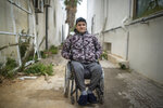 Khaled Benneejma, 32, a protester who was paralyzed after being shot during Tunisia's democratic uprising 10 years ago, poses for a portrait in Tunis, Tunisia, Tuesday, Jan. 12, 2021. (AP Photo/Mosa'ab Elshamy)