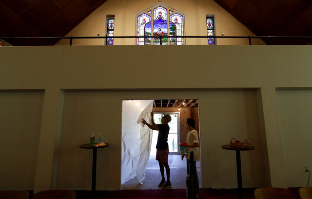 Alamo Heights Baptist Church pastor Bobby Contreras, left, and his wife Hannah, work to clean, sanitize and prepare the church for services this Sunday, in San Antonio, Wednesday, May 6, 2020,. Texas' stay-at-home orders due to the COVID-19 pandemic have expired and Texas Gov. Greg Abbott has eased restrictions on many businesses that have now opened, churches and places or worship may resume live services with 25% capacity. (AP Photo/Eric Gay)
