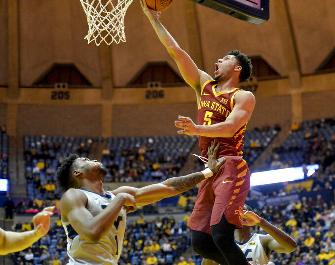 Iowa State guard Lindell Wigginton (5) goes up for a layup over West Virginia forward Derek Culver (1) during the second half of an NCAA college basketball game Wednesday, March 6, 2019, in Morgantown, W.Va. (William Wotring/The Dominion-Post via AP)