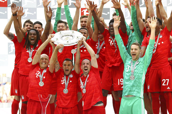 Front from left, Bayern's Arjen Robben, Rafinha, Franck Ribery and Manuel Neuer lift the trophy to celebrate Bayern's 7th straight Bundesliga title after the German Soccer Bundesliga match between FC Bayern Munich and Eintracht Frankfurt in Munich, Germany, Saturday, May 18, 2019. (AP Photo/Matthias Schrader)