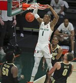 Miami forward Anthony Walker (1) dunks over Purdue defenders during the second half of an NCAA college basketball game Tuesday, Dec. 8, 2020, in Coral Gables, Fla. (Al Diaz/Miami Herald via AP)