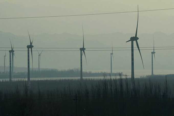 Windmills are seen from a high speed train traveling from Beijing to neighboring Zhangjiakou in northwestern China's Hebei province on Dec. 15, 2020. Expectations are high that the 14th five-year plan will align domestic policies with international pledges on climate change. Chinese President Xi Jinping made a surprise pledge at a United Nations meeting in September that China would go carbon neutral by 2060. (AP Photo/Ng Han Guan)