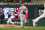 Milwaukee Brewers pitcher Adrian Houser, center, walks off the mound as Minnesota Twins' Brent Rooker, right, heads home on a bases-loaded walk off Houser of Twins' Luis Arraez as Andrelton Simmons, second from back left, heads to second base in the fourth inning of a baseball game Saturday, Aug. 28, 2021, in Minneapolis. (AP Photo/Jim Mone)