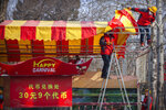 Workers dismantle a carnival built for a canceled Lunar New Year temple fair at Longtan Park in Beijing, Saturday, Jan. 25, 2020. China's most festive holiday began in the shadow of a worrying new virus Saturday as the death toll surpassed 40, an unprecedented lockdown kept 36 million people from traveling and authorities canceled a host of Lunar New Year events. (AP Photo/Mark Schiefelbein)