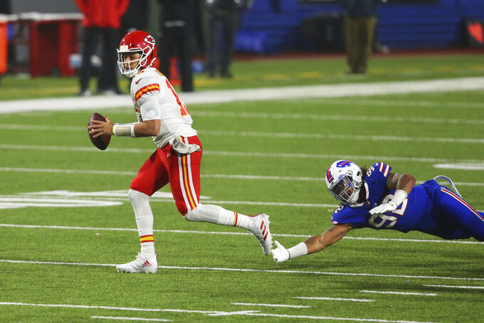 Kansas City Chiefs quarterback Patrick Mahomes, left, outruns Buffalo Bills' Darryl Johnson during the second half of an NFL football game, Monday, Oct. 19, 2020, in Orchard Park, N.Y. (AP Photo/Jeffrey T. Barnes)