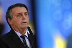Brazil's President Jair Bolsonaro speaks at a ceremony announcing economic measures to support philanthropic hospitals and help them treat COVID-19 patients, at the Planalto Presidential Palace, in Brasilia, Brazil, Thursday, March 25, 2021. (AP Photo/Eraldo Peres)