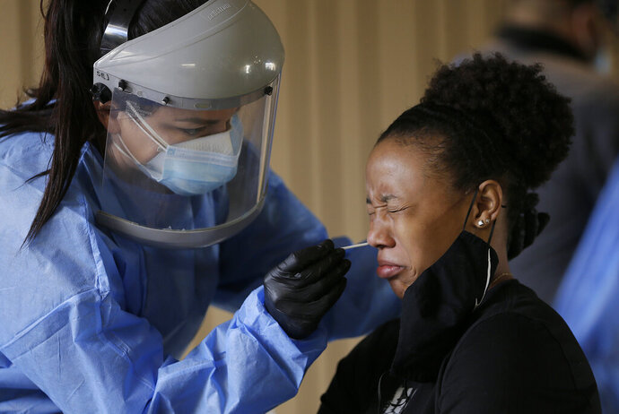 Sasha Jacquez tests The University of Texas at El Paso student Ariona Gill for coronavirus Friday, Oct. 16, 2020, at the UTEP Fox Fine Arts Center in El Paso, Texas. Deaths per day from the coronavirus in the U.S. are on the rise again, just as health experts had feared, and cases are climbing in nearly every single state. In El Paso, authorities instructed people to stay home for two weeks and imposed a 10-p.m.-to-5-a.m. curfew because of a surge that has overwhelmed hospitals. (Mark Lambie/The El Paso Times via AP)