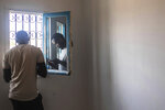 In this Monday, Sept. 23, 2019 photo, Abdullah, 25, a Sudanese migrant who tried crossing the Mediterranean from Libya, is reflected in a window as he uses his phone inside a Tunisian Red Crescent facility in Zarzis, southern Tunisia. The group of 47 in his first crossing from Tripoli over a year earlier had paid a uniformed Libyan and his cronies $127,000 in a mix of dollars, euros and Libyan dinars for the chance to leave their detention center and cross in two boats. They were intercepted in a coast guard boat by the same uniformed Libyan, shaken down for their cell phones and more money, and tossed back into detention. (AP Photo/Mosa'ab Elshamy)