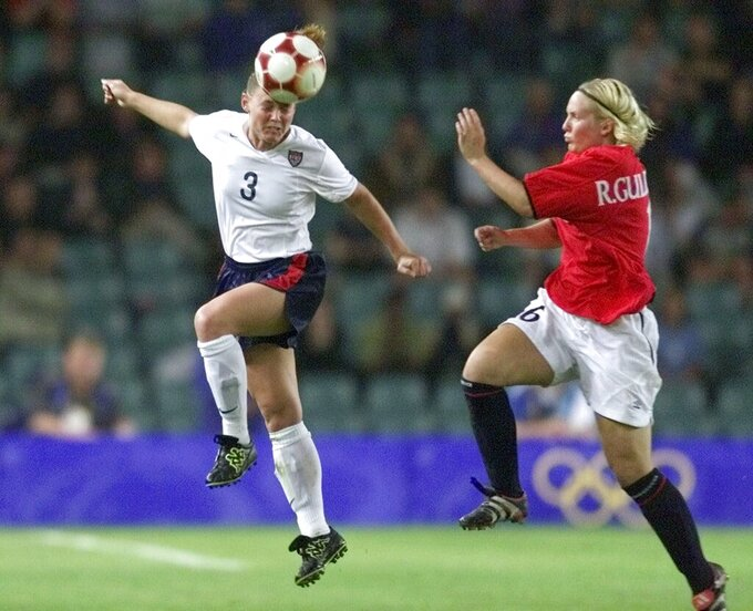 FILE - In this Sept. 28, 2000, file photo, United States' Christie Pearce, left, heads the ball as Norway's Ragnhild Gulbrandsen defends during the women's soccer final at the Summer Olympics in Sydney. American national team defenders Steve Cherundolo and Pearce have been elected to the U.S. National Soccer Hall of Fame. (AP Photo/Ricardo Mazalan, File)