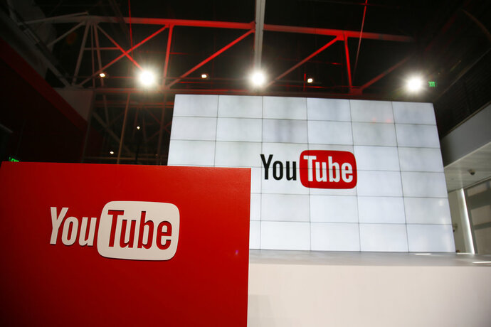 FILE - This Oct. 21, 2015, file photo shows signage inside the YouTube Space LA offices in Los Angeles.YouTube says it's cracking down on conspiracy videos, though it's scant on the details. YouTube CEO Susan Wojcicki said at a conference on Tuesday, March 13, 2018, that the company will work to debunk videos espousing conspiracy theories by including links to the online encyclopedia Wikipedia. (AP Photo/Danny Moloshok, File)