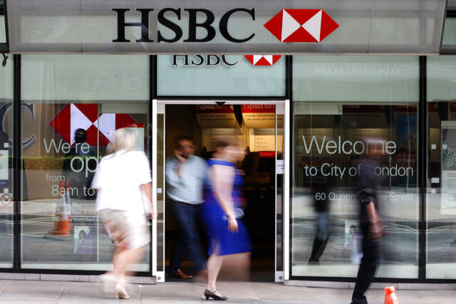FILE - In this Aug. 28, 2015, file photo, people walk past a branch of HSBC bank in London. Europe's biggest bank, HSBC, has reported Monday, Aug. 3, 2020, its net profit plummeted 96% in the second quarter of this year as lower interest rates combined with the downturn due to the coronavirus pandemic stunted business activity.  (AP Photo/Frank Augstein, File)