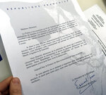A document signed by French President Emmanuel Macron and given to Britain's Catherine Norris Trent holds is pictured during a naturalization ceremony in Paris' Pantheon monument, Thursday, March 21, 2019. With the looming Brexit deadline, the 38-year-old mother of two who's lived in the French capital for over a decade was one of dozens of newly-minted French nationals attending the ceremony. (AP Photo/Thomas Admason)