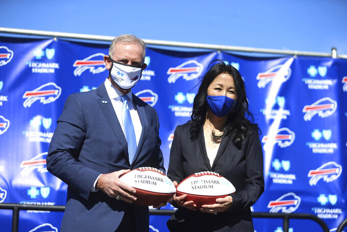 Highmark Blue Cross Blue Shield of Western New York CEO Dave Anderson and Bills owner and president Kim Pegula hold footballs with the new stadium name at Highmark Stadium, home of the Buffalo Bills, in Orchard Park, N.Y., Tuesday, March 30, 2021. (John Hickey/Buffalo News via AP)