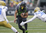 Oregon's Travis Dye, center, rushes against UCLA during the second quarter of an NCAA college football game Saturday, Nov. 21, 2020, in Eugene, Ore. (AP Photo/Chris Pietsch)