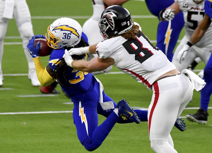 Strong safety Jahleel Addae, left, of the Los Angeles Chargers intercepts a pass intended for tight end Jaeden Graham, right, of the Atlanta Falcons in the fourth quarter of an NFL football game in Inglewood on Sunday, Dec. 13, 2020. (Keith Birmingham/The Orange County Register via AP)