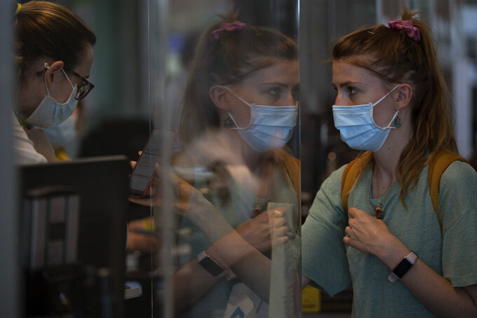 Passengers check their luggage at Barcelona airport, Spain, Monday, June 7, 2021. Spain is trying to ramp up its tourism industry by welcoming from Monday vaccinated visitors from most countries, as well as all Europeans who prove that they are not infected with the coronavirus. (AP Photo/Emilio Morenatti)