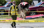 A member of the Canadian Forces walks past the tail section of a crashed Snowbird jet in Kamloops, British Columbia, Monday, May 18, 2020. Capt. Jennifer Casey died Sunday after the Snowbirds jet she was in crashed shortly after takeoff. The pilot of the aircraft is in hospital with serious injuries. (Jonathan Hayward/The Canadian Press via AP)