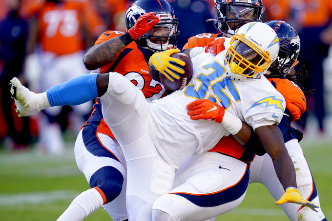 Los Angeles Chargers running back Troymaine Pope (35) is tackled by Denver Broncos inside linebacker A.J. Johnson during the first half of an NFL football game, Sunday, Nov. 1, 2020, in Denver. (AP Photo/David Zalubowski)