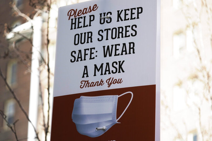 A sign requiring face masks is seen at Harmons Grocery store Monday, March 8, 2021, in Salt Lake City. Utah's statewide mask mandate will be lifted on April 10 under a measure that passed the full Legislature Friday, March 5, 2021. Republican Gov. Spencer Cox has said he plans to sign the bill. The bill lays out a new timeline for when Utah's COVID-19 restrictions applying to businesses, events, and schools would end. The mask mandate would still apply to gatherings of more than 50 people. (AP Photo/Rick Bowmer)