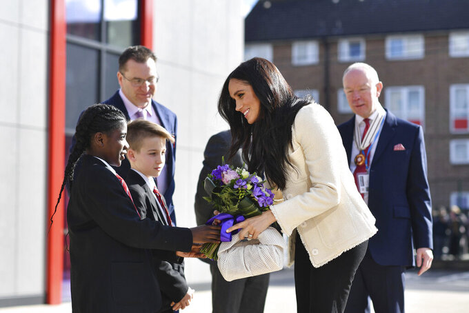 """FILE - In this Friday, March 6, 2020, file photo, Britain's Meghan, Duchess of Sussex, is greeted by pupils at the Robert Clack Upper School in Dagenham, Essex, in eastern London, during a surprise visit to celebrate International Women's Day. Meghan and Prince Harry's second Netflix project will focus on a 12-year-old girl's adventures in an animated series. The Duke and Duchess of Sussex's Archewell Productions announced Wednesday, July 14, 2021, that the working title """"Pearl"""" will be developed for the streaming service. (Ben Stansall/Pool via AP, File)"""