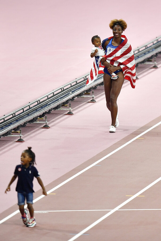 Nia Ali, of the United States, celebrates with her baby after winning the the women's 100 meter hurdles at the World Athletics Championships in Doha, Qatar, Sunday, Oct. 6, 2019. (AP Photo/Martin Meissner)
