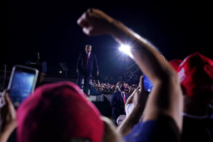 Supporters cheer as President Donald Trump leaves after speaking at a campaign rally at Middle Georgia Regional Airport, Friday, Oct. 16, 2020, in Macon, Ga. (AP Photo/Evan Vucci)