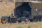 Israeli soldiers sit by shells next to an Israeli mobile artillery unit placed in northern Israel near the border with Lebanon, Tuesday, July 28, 2020. Israeli forces have exchanged fire with Hezbollah militants along the volatile Israeli-Lebanese frontier. (AP Photo/Ariel Schalit)