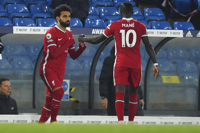 Liverpool's Sadio Mane, right, is replaced by Liverpool's Mohamed Salah during the English Premier League soccer match between Leeds United and Liverpool at the Elland Road stadium in Leeds, England, Monday, April 19, 2021. (Paul Ellis/Pool via AP)