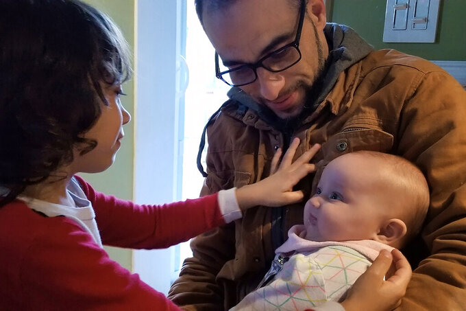 In this March 2019 photo provided by Allison Andrade-Cullen, her husband Flavio Andrade Prado, a Brazilian national, top right, holds their daughter Saoirse Andrade-Cullen, right, as their son Gabriel Andrade-Cullen, left, looks on at their home, in Brockton, Mass., as Andrade Prado prepares to leave for work. Andrade Prado is being held by Immigration and Customs Enforcement, or ICE, at the Plymouth County House of Corrections. The number of detainees nationwide has more than doubled since the end of February, to nearly 27,000, according to recent data from U.S. Immigration and Customs Enforcement. (Allison Andrade-Cullen via AP)