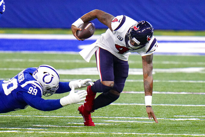 Houston Texans quarterback Deshaun Watson (4) escapes from Indianapolis Colts defensive tackle DeForest Buckner (99) in the first half of an NFL football game in Indianapolis, Sunday, Dec. 20, 2020. (AP Photo/AJ Mast)