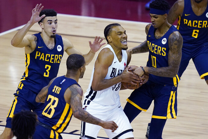 Portland Trail Blazers' George King drives against Indiana Pacers' Devin Robinson, right, and Chris Duarte, left, during the first half of an NBA summer league basketball game Thursday, Aug. 12, 2021, in Las Vegas. (AP Photo/John Locher)