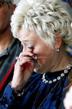 Cindy Leech wipes her eye during a news conference by Pennsylvania Attorney General Josh Shapiro, Friday, Jan. 11, 2019, in Brookville, Pa. Her son, Corey Leech, who died in 2017, had anonymously testified that he was sexually abused by Brother Stephen Baker, when Leech was a student at what was then Bishop McCort High School. His testimony was used in the damning Pennsylvania grand jury report that named almost 300 predator priests accused abusing more than 1,000 victims in six of the state's dioceses. (AP Photo/Keith Srakocic)