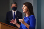 Dr. Mandy Cohen, secretary of the state Department of Health and Human Services, holds up a mask while speaking during a briefing at the Emergency Operations Center in Raleigh, N.C., Thursday, July 9, 2020. (Ethan Hyman/The News & Observer via AP)