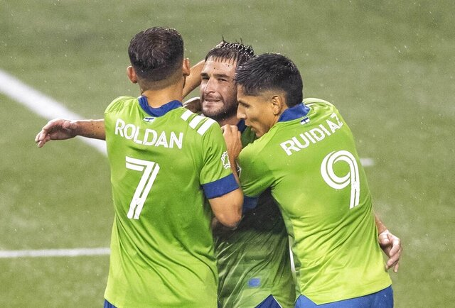 Seattle Sounders gather around captain Nicolas Lodeiro, center, after he scored the second of two penalty kicks in the first half of an MLS soccer match against Los Angeles FC, Friday, Sept. 18, 2020, in Seattle. (Dean Rutz/The Seattle Times via AP)