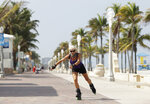 A rollerblader skates on the Broadwalk on Hollywood beach, Tuesday, May 19, 2020, in Hollywood, Fla. Broward County started a phased reopening Monday. (AP Photo/Wilfredo Lee)