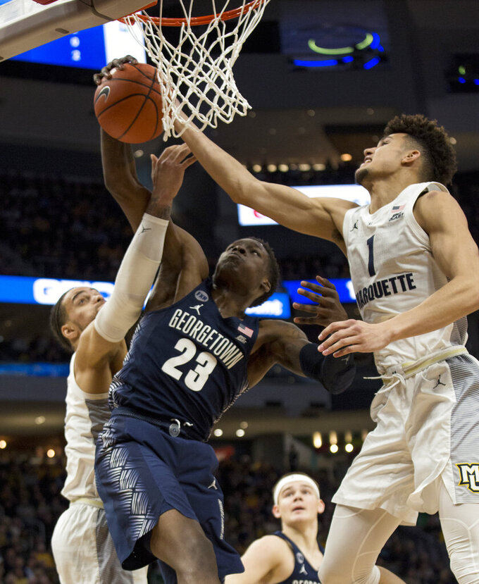 Georgetown forward Josh LeBlanc, center, battles for the rebound against Marquette forward Theo John, left, and forward Brendan Bailey, right, during the first half of an NCAA college basketball game Saturday, March 9, 2019, in Milwaukee. (AP Photo/Darren Hauck)