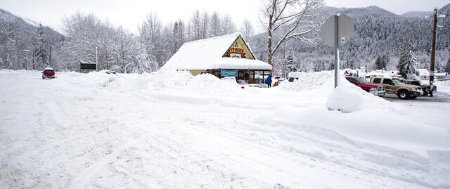 Snow covers the land by Steven's Pizza in Skykomish, Wash., along Highway 2, Wednesday, Jan. 15, 2020, in Skykomish, Wash. Volunteers brought food and supplies here for local Skykomish residents stranded without power or access to food. (Mike Siegel/The Seattle Times via AP)
