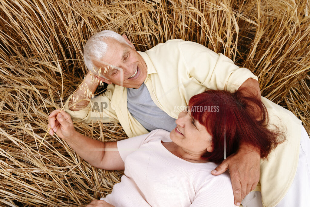 Smiling senior couple resting on wheat field