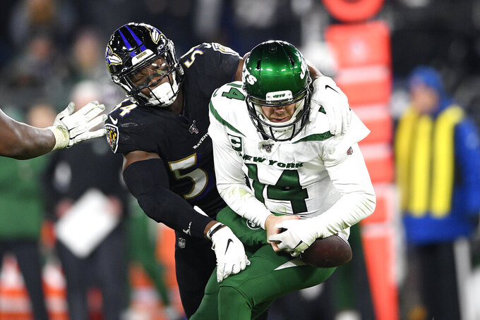 Baltimore Ravens linebacker Tyus Bowser, left, forces a fumble off New York Jets quarterback Sam Darnold during the second half of an NFL football game, Thursday, Dec. 12, 2019, in Baltimore. (AP Photo/Nick Wass)