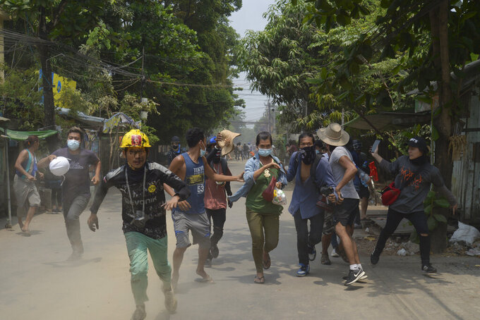 Anti-coup protesters run to avoid the military during a demonstration in Yangon, Myanmar on Tuesday March 30, 2021. (AP Photo)