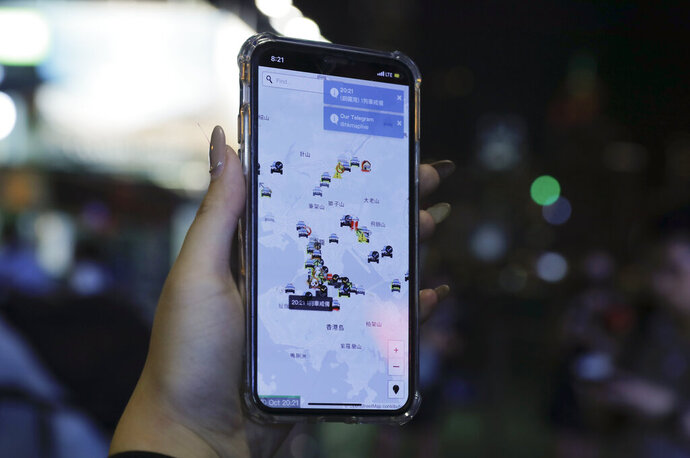 A person's phone shows HKmap.live apps as they join others at a rally to mark Taiwan's National Day, in the Tsim Sha Tsui district in Hong Kong, Thursday, Oct. 10, 2019.  A Hong Kong government official said on Thursday that Apple was responsible for removing a smartphone application which allowed activists to report police movements. (AP Photo/Kin Cheung)