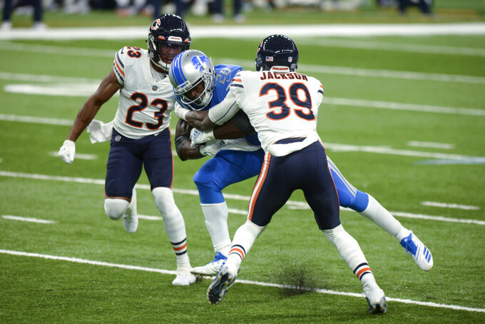 Detroit Lions running back Adrian Peterson (28) runs between Chicago Bears free safety Eddie Jackson (39) and cornerback Kyle Fuller (23) in the first half of an NFL football game in Detroit, Sunday, Sept. 13, 2020. (AP Photo/Jose Juarez)