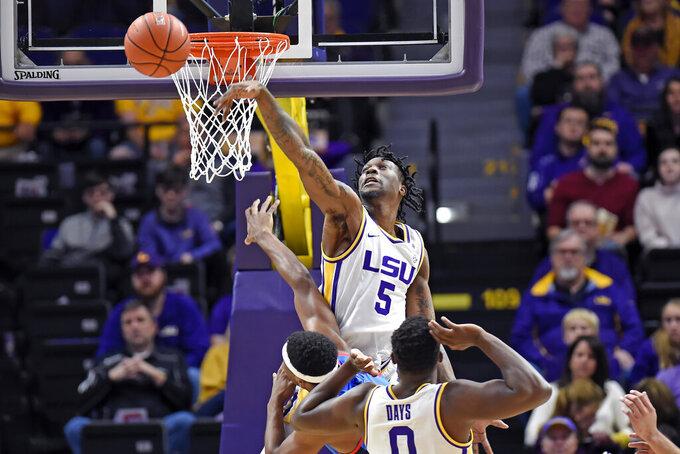 LSU forward Emmitt Williams (5) blocks the shot of Mississippi forward Blake Hinson (0) as LSU forward Darius Days (0) watches in the first half of an NCAA college basketball game, Saturday, Feb. 1, 2020, in Baton Rouge, La. LSU won 73-63. (AP Photo/Bill Feig)