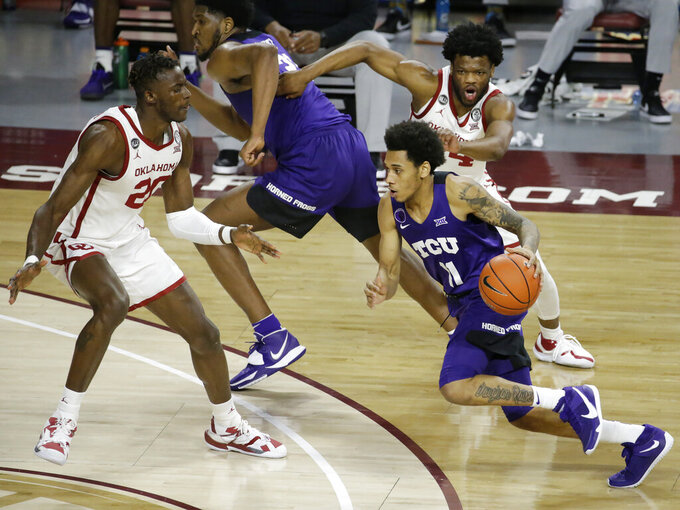 TCU's Taryn Todd (11) drives against Oklahoma's Rick Issanza (20) and Elijah Harkless (24) while TCU's Kevin Samuel (21) runs into position during the second half of an NCAA college basketball game in Norman, Okla., Tuesday, Jan. 12, 2021. (AP Photo/Garett Fisbeck)