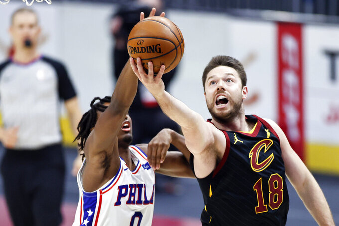 """FILE - In this April 1, 2021, file photo, Cleveland Cavaliers' Matt Dellavedova (18) shoots ahead of Philadelphia 76ers' Tyrese Maxey (0) in the first half of an NBA basketball game in Cleveland. The former feisty Cavaliers guard signed a three-year contract Friday, July 9, 2021, with Melbourne United, the defending champion in Australia's National Basketball League. Dellavedova, affectionately known as """"Delly"""" to his teammates and fans, had two stints over six seasons with Cleveland, which signed him as an undrafted free agent in 2013 (AP Photo/Ron Schwane, File)"""