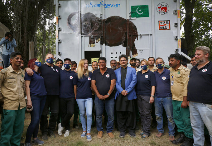 Pakistani wildlife workers, officials and experts from the international animal welfare organization Four Paws, pose for photograph next to a crate holding an elephant named Kaavan before he is transported to a sanctuary in Cambodia, at the Marghazar Zoo in Islamabad, Pakistan, Sunday, Nov. 29, 2020. Kavaan, the world's loneliest elephant, became a cause celebre in part because America's iconic singer and actress Cher joined the battle to save him from his desperate conditions at the zoo. (AP Photo/Anjum Naveed)