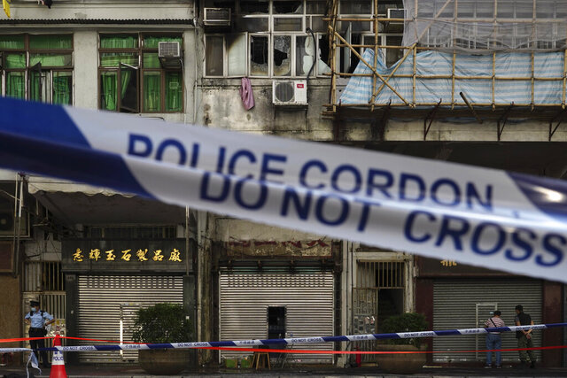 A police cordon line is set at a fire site, top center with broken windows, in Hong Kong Monday, Nov. 16, 2020. City authorities said a fire in a crowded residential district in Hong Kong has